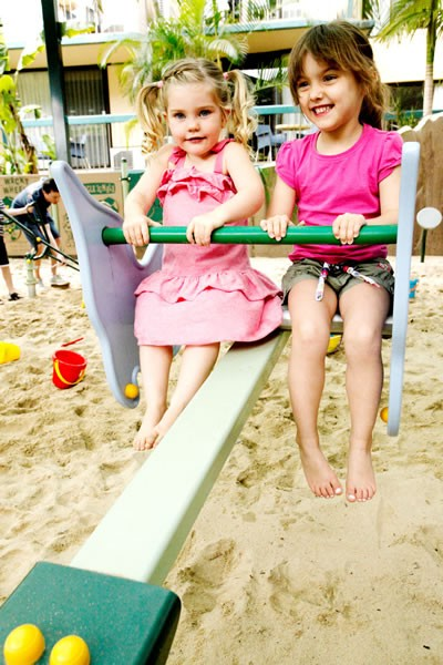 Two little girls on a seesaw at Paradise Resort, Surfers Paradise.