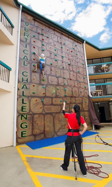 Little boy rock climbing wall at Paradise Resort with Childcare Belayer.