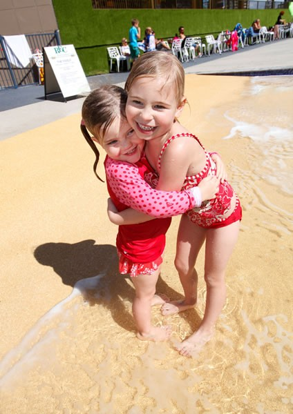 Two little girls hugging at the Paradise resort pool.