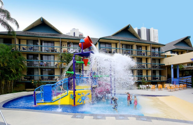 Kids playing under the water tipping out of the giant bucket at the water park at Paradise Resort.
