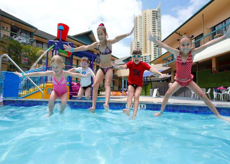 Kids jumping into the Pool at paradise resort.
