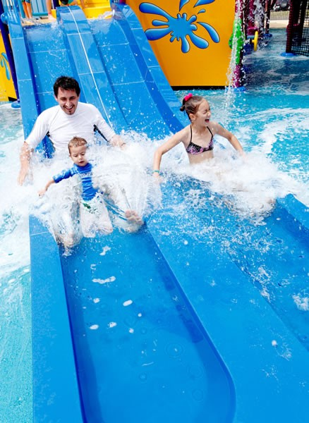Dad and two kids having fun riding down the water slide at Paradise Resort