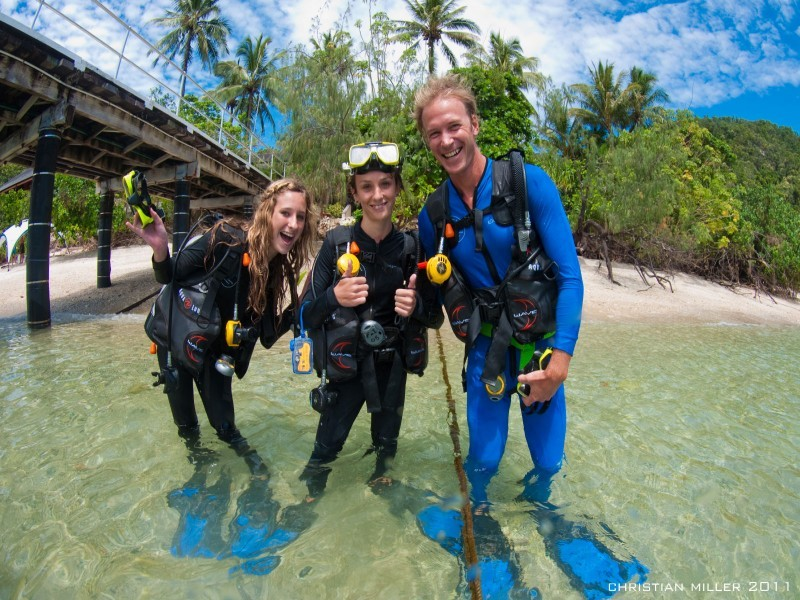 Three divers scuba diving on the Great Barrier reef posing for photo on the shore.