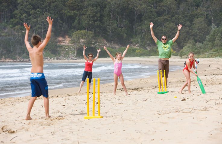Family playing beach cricket at the Gold Coast.