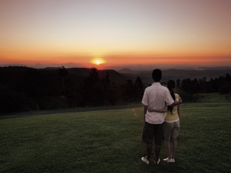 Couple enjoying the beautiful sunset over O'Reilly's Rainforest Retreat - Discover Queensland