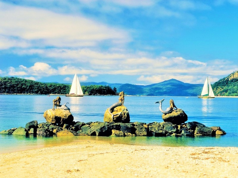 Three Mermaid Statues on Daydream Island overlooking the mountains and ocean - Discover Queensland