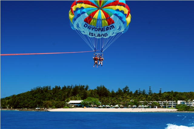 Daydream Island Couple Parasailing over the ocean  - Discover Queensland