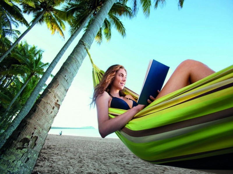 Lady enjoying a book on a hammock on the beach at Port Douglas.