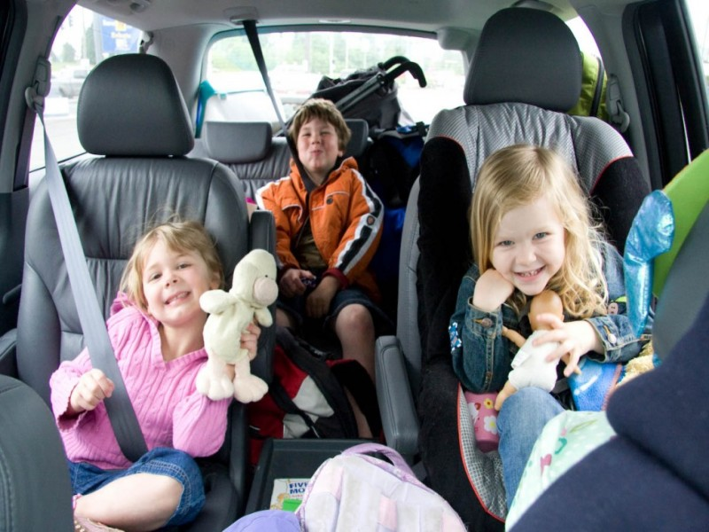 Three kids in seat belts playing games on car trips.