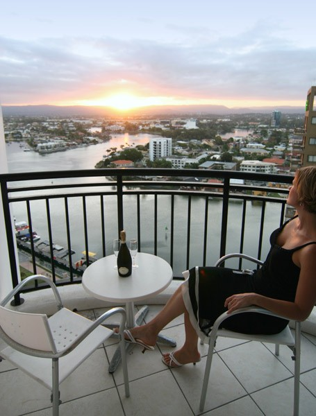 Lady relaxing on the Balcony of the Chevron Renaissance enjoying a sunset over champagne.