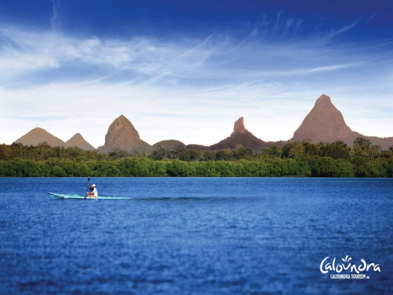 Kayaking in Caloundra with the Glasshouse Mountains in the background.