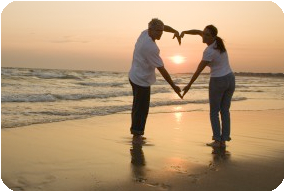 Couple on a Romantic Beach Getaway making a heart with their arms.