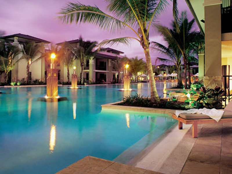 The flame-lit lagoon pool at Sea Temple Private Apartments by Boutique Collection in Port Douglas | Discover Queensland